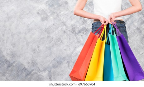 Colourful shopping bags and woman hand on copy space background