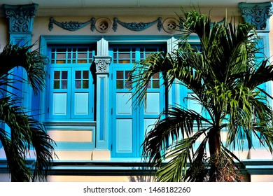 Colourful Singapore Peranakan or Straits Chinese shop house with stone carving, blue exterior, antique blue shutters and framed by palm trees in downtown Singapore