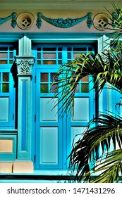 Colourful Singapore Peranakan or Straits Chinese shop house with stone carving, blue exterior, antique blue shutters and framed by palm tree in downtown Singapore