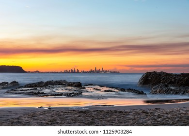 Colourful smokey red sunset in the skies over Surfers Paradise Gold Coast cityscape. View from Currumbin Rock Gold Coast.