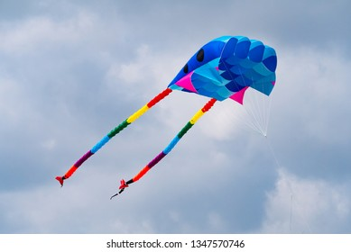 Colourful soft kite flying with a cloudy sky background.
