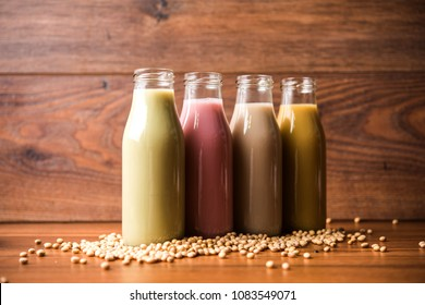 colourful Soya OR Soy milk made by soaking and grinding soybeans, it's a healthy drink served in a bottle with raw whole in a bowl