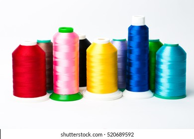 Colourful spools of thread on white background