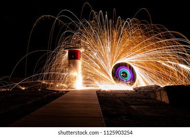 Colourful steelwool lights near lighthouse pole at Gold Coast Spit