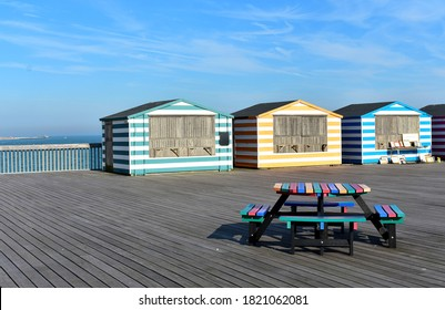 Colourful stripy beach huts and a picnic table on Hastings pier. The huts were closed for the day, emptying the pier from people.