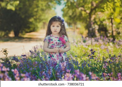 colourful summer scene of cute runette young girl child enjoying free time in wild forest flowers field wearing stylish tiny dress on sunny meadow.
