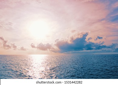 Colourful sun rises above the sea in gold, pink and blue colours with horizon and puffy clouds