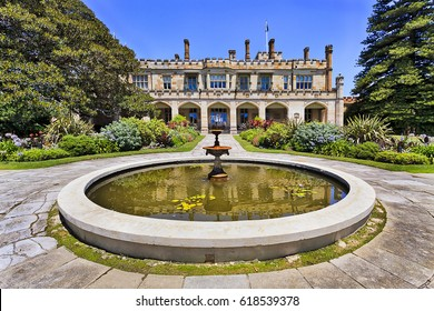 Colourful sunny summer day in Royal Botanic garden of Sydney with fountain and view on historic colonial public heritage building.