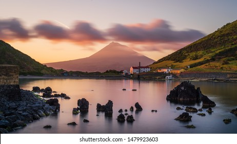Colourful Sunrise in Horta, Faial Island: long Exposure of the Porto Pim Beach, the Whaling Station and the Pico Volcano Mountain in the background, Azores Islands, Portugal.