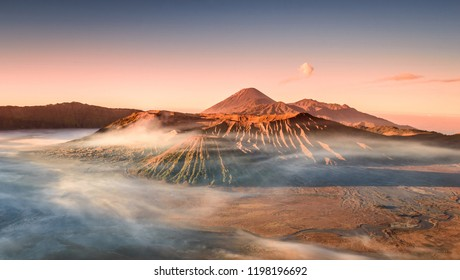 Colourful sunrise at the Mount Bromo, King Kong Hill Viewpoint. Wideangle panorama shot of amazing daybreak in Gunung Bromo active volcano in Java, Indonesia. Morning mist inversion photography.
