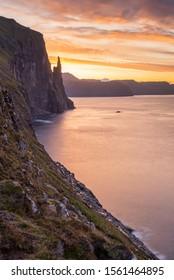 A colourful sunrise and skyline lighting up the Atlantic Ocean and coastline by Trøllkonufingur or Troll Woman's Finger over at Vagar, Faroe Islands.