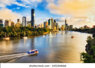 Colourful sunrise and soft morning sun light in Brisbane city over Brisbane river and high-rise CBD towers from elevation of Kangaroo point and Cliffs park.