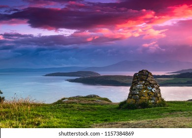 Colourful sunset looking over the Cumbrae Isles towards Arran, on the West coast of Scotland. A stone cairn is prominent in the foreground