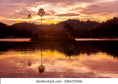 Colourful sunset on the lake in Kandi, Sri Lanka with silhouettes of trees and mirror reflection in the water