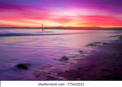 Colourful sunset over the sea at a beach in the evening at Exmouth, Devon, UK. The tide slowly comes in as the sun sets. Waves lap gently on the beach at twilight.