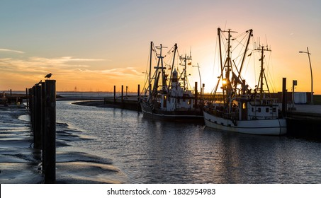 Colourful sunset at the small harbour with crab boats in Wremen near Cuxhaven, Germany