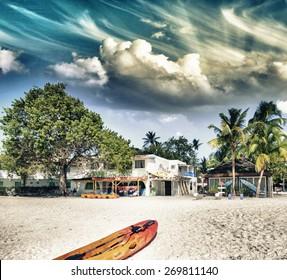 Colourful surfboard on a tropical sunny beach.