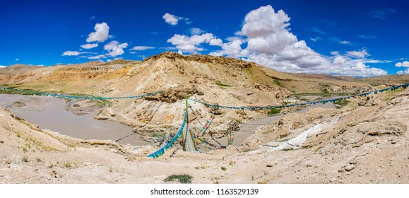 Colourful Tibetan prayful flags flutter on wind in sacred Garuda valley and Guge kingdom in Ngari, West Tibet. Old bridge over Sutlej river. Sacred place for Buddha pupils making piligrimage in Asia.