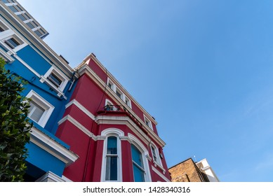 Colourful townhouses in Notting Hill, London, England, UK. Low angle view against sky