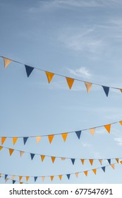 Colourful triangle flages on blue sky background.