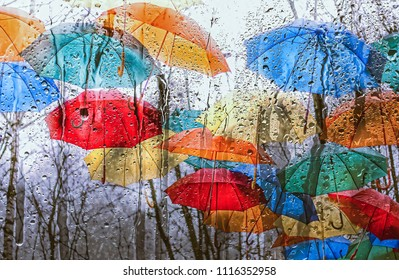 colourful umbrellas over rainy window. texture of autumn umbrellas and wet glass. autumn season. rain outside window on rainy  autumn day.  texture of raindrops, wet glass. autumn season