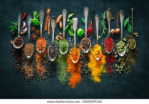 Красочные различные травы и специи для приготовления пищи на темном фоне