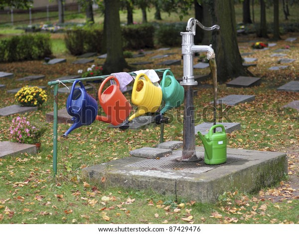 Colourful watering cans hanging at a hand pump on a cemetery in Thuringia in Germany. The brilliant colours form a vivid contrast to the autumnal trees.