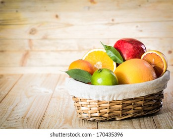 Colourful wicker basket of assorted tropical fruit with a lime, grapefruit, oranges and an apple in a country kitchen on wooden boards