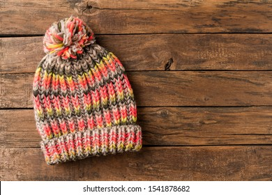 Colourful winter hat with pompon on rustic wooden background with copyspace. Top view