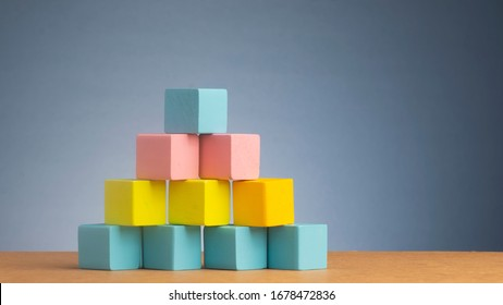 Colourful of wooden blocks stacked like pyramid.