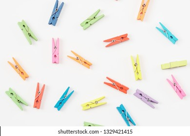 Colourful wooden clothespins are randomly scattered on white background, close up.