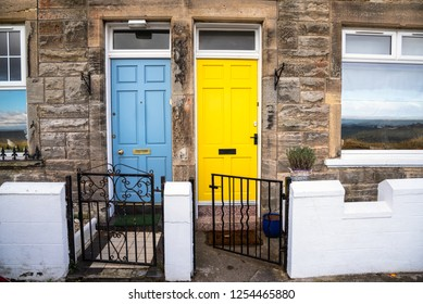 Colourful Wooden Front Doors of two traditional British Stone Terraced Houses. One Door is Light Blue while the other is Bright Yellow.