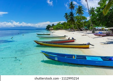 Colourful wooden motor boats tied up on the beach at a remote fishing village, Raja Ampat Regency, West Papua, Indonesia.