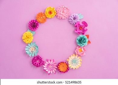 Colourful wreath made of handmade paper flowers on pink background