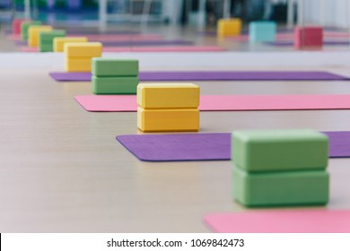 Colourful yoga blocks and mats place on wooden texture floor. Ready for yoga class.