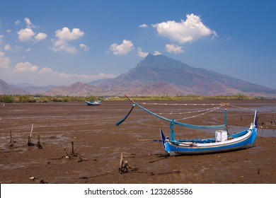 Colourfull fishing wooden boat stranded on mud because of low tide with blue sky and a mountain background in east java ocean