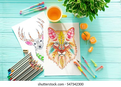 Colouring pictures, pencils and pens on wooden table