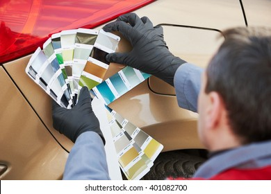 colourist man selecting color of car with paint matching samples