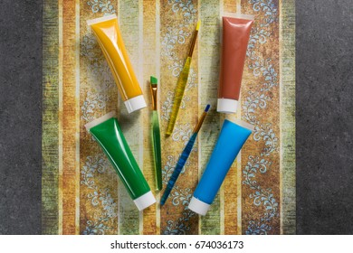 Colours of the nature - mix of green, blue, yellow and brown - home or office interieur design concept, tubes with acrylic paint and  brush, close up