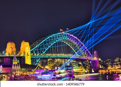 Colours on steel arch of the Sydney Harbour bridge sending blue laser lights to dark night sky over Sydney harbour waters during Vivid Sydney light show.