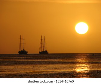 Colours of the Sku during sunset on the beach with Silhouette of boats with sails