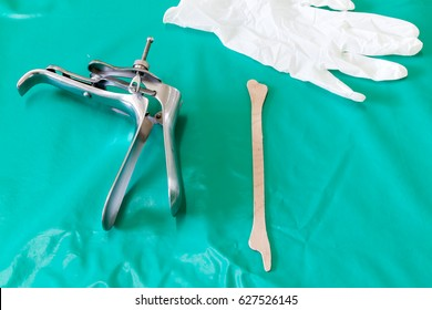 Colposcop, spatula and Medical gloves on a clean green blanket (Equipment vaginal speculum) for (Pap smear) gynecology inspect EXAMINATION Cervical cancer