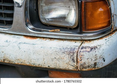 Colse up to decay and rust on the front bumper of an old white truck. Rust hole on old worn painted metal surface.
