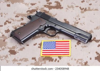 colt 1911 handgun on camouflage uniform