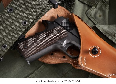 Colt pistol in a holster and belt lie on military jacket closeup
