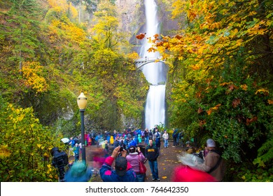 Columbia Gorge, Oregon -  11/7/20: Multnomah Falls and foot bridge  in the Columbia River Gorge National Scenic Area, Oregon.  A crowd of tourists  gathered at the main viewpoint.