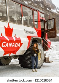 COLUMBIA ICEFIELD, ALBERTA, CANADA - JUNE 2018: Person standing next a huge purpose-built vehicle which takes tourists onto the Athabasca Glacier in the Columbia Icefield in Canada.