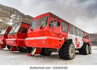 COLUMBIA ICEFIELD, ALBERTA, CANADA - JUNE 2018: Three massive six wheel purpose-built vehicles which take tourists onto the Athabasca Glacier in the Columbia Icefield in Alberta, Canada.