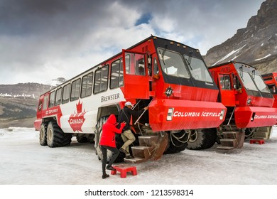 COLUMBIA ICEFIELD, ALBERTA, CANADA - JUNE 2018: Tourists climbing aboard a massive six wheel purpose-built vehicle on the Athabasca Glacier in the Columbia Icefield in Alberta, Canada.