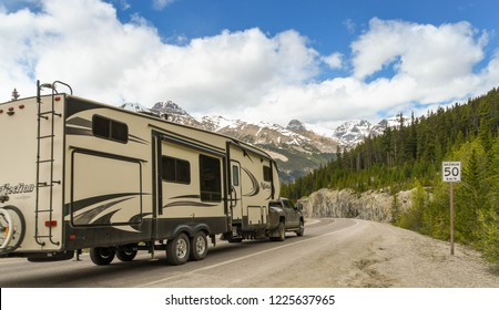 COLUMBIA ICEFIELD, ALBERTA, CANADA - JUNE 2018: Truck towing a big camping trailer on a road through the Columbia Icefield area in Alberta, Canada.